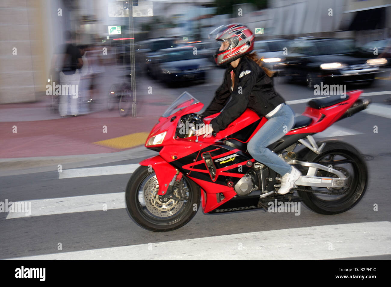 Miami Beach Florida Collins Avenue woman motorcycle bike crotch rocket red helmet motion two-wheel sports speed - Stock Image