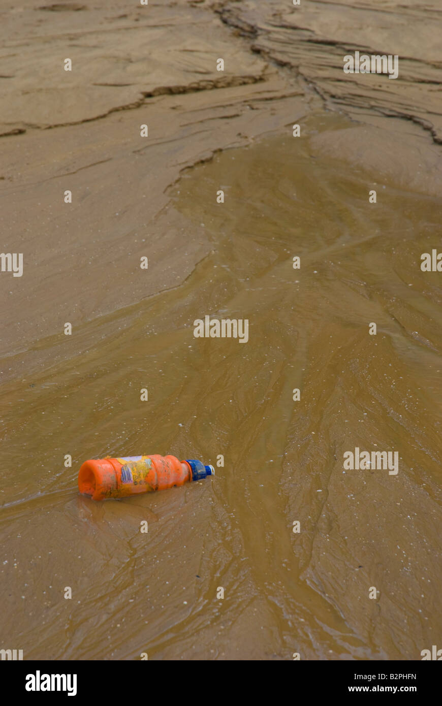 Washed up bottle on beach - Stock Image