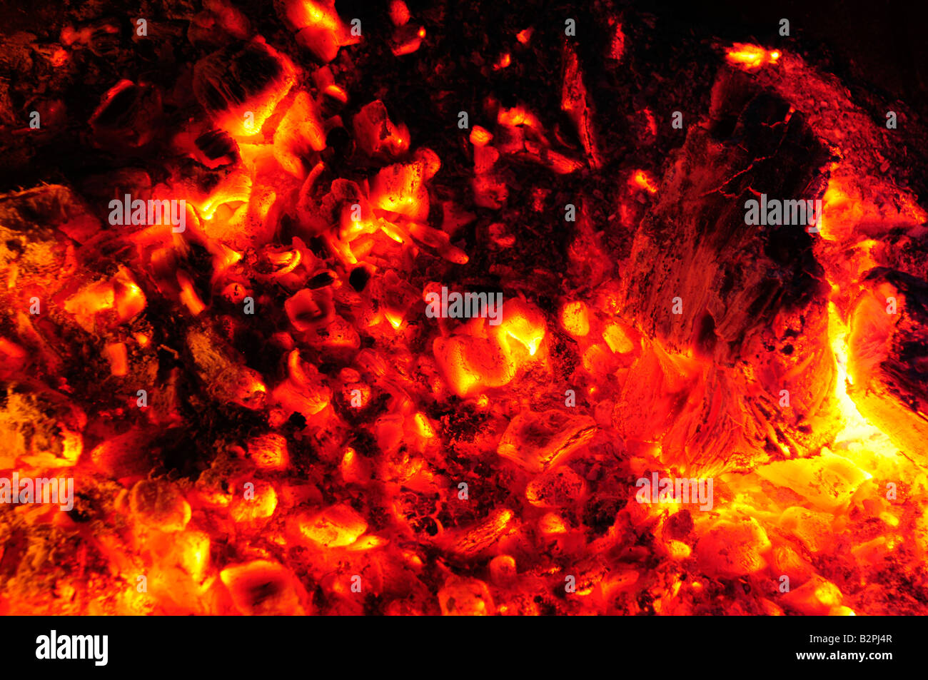 Glowing embers of a fire turning molten - Stock Image