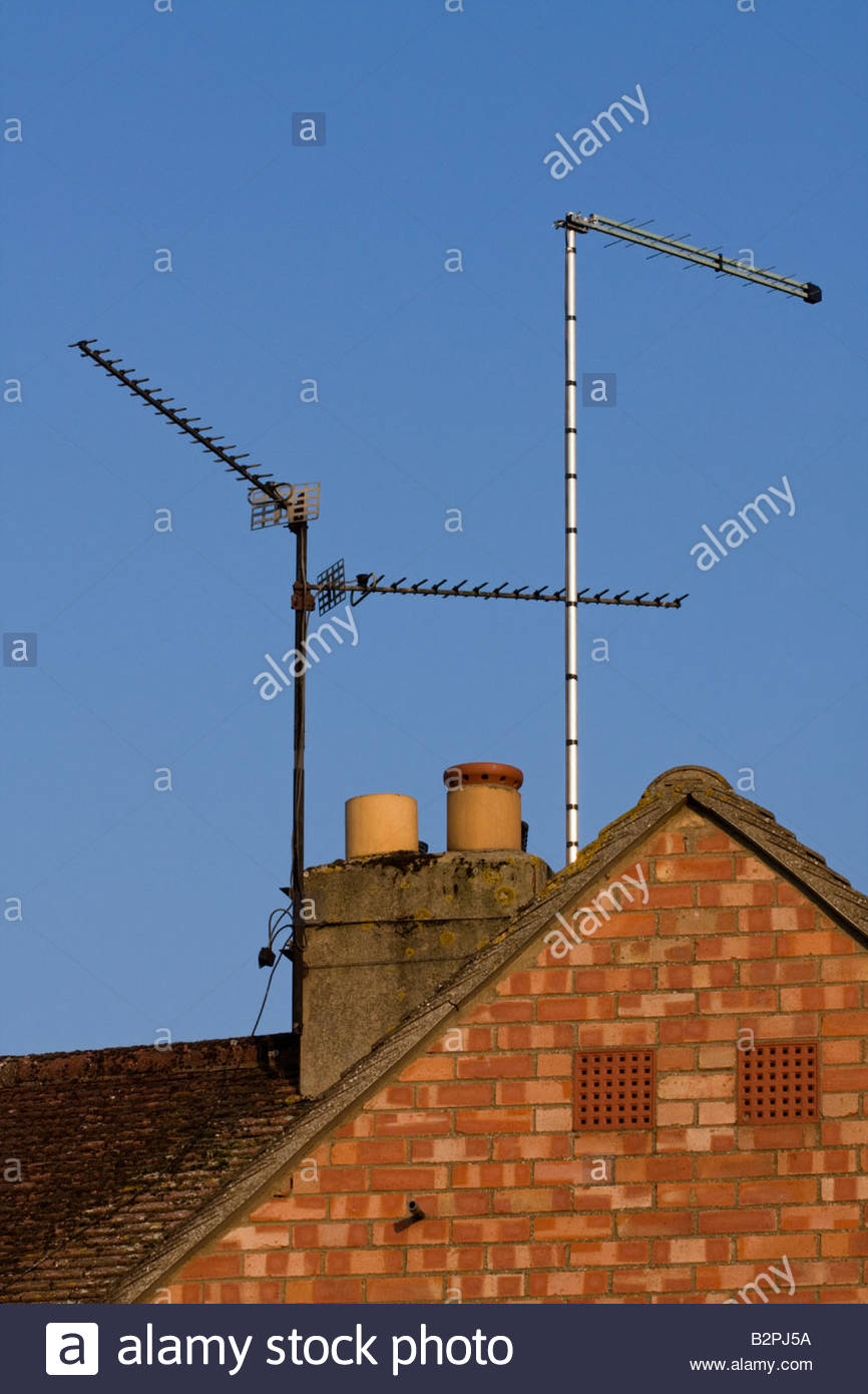 TV aerials on roof top - digital and analogue - Stock Image