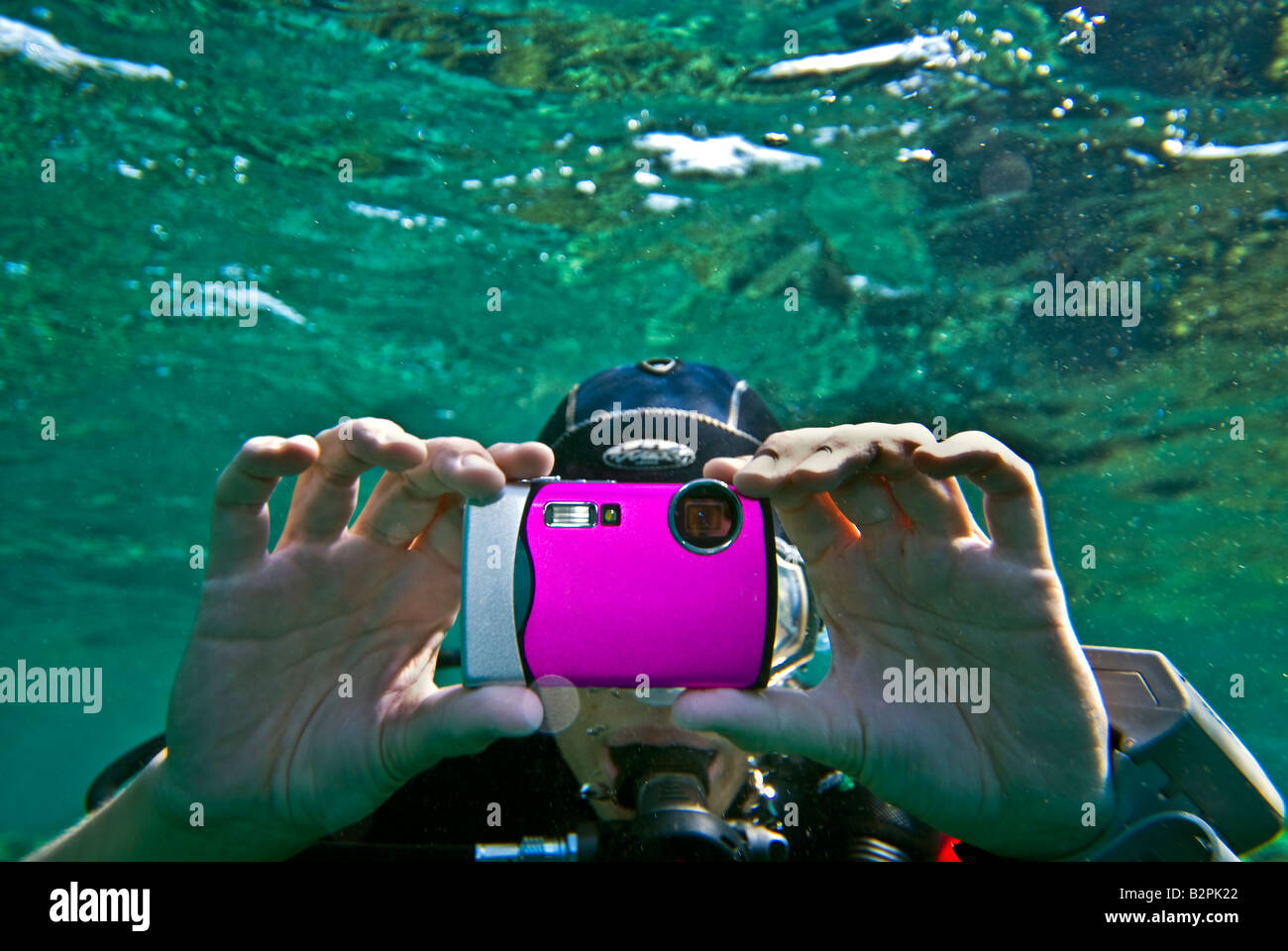 girl woman she DIVER underwater photographer taking pictures camera small compact tight diver dive pink lilac lila - Stock Image