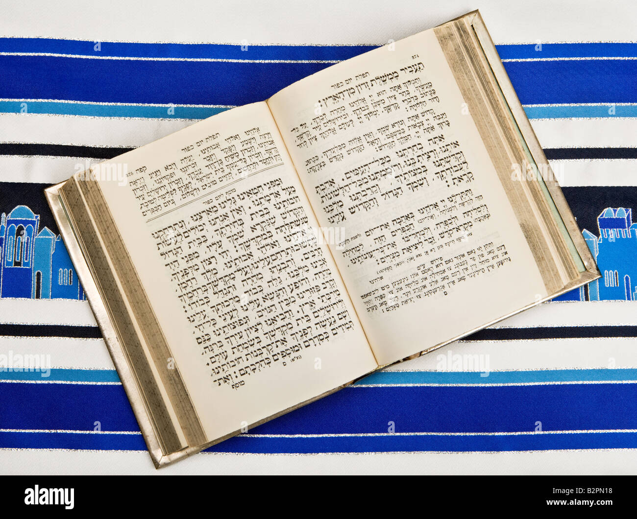 A Jewish prayer book, or Siddur, open and on top of a Jewish prayer shawl, or Tallit - Stock Image