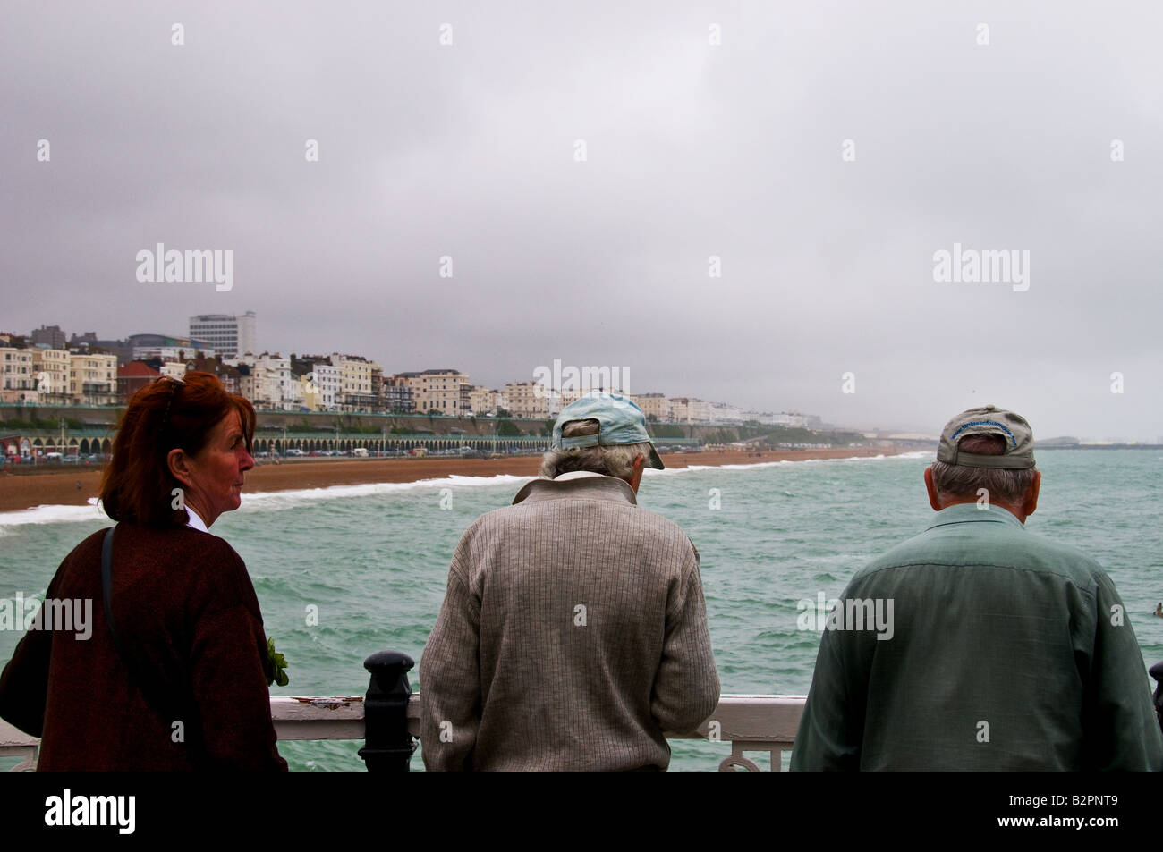 Three people standing on Brighton Pier in West Sussex on a windy overcast day. - Stock Image