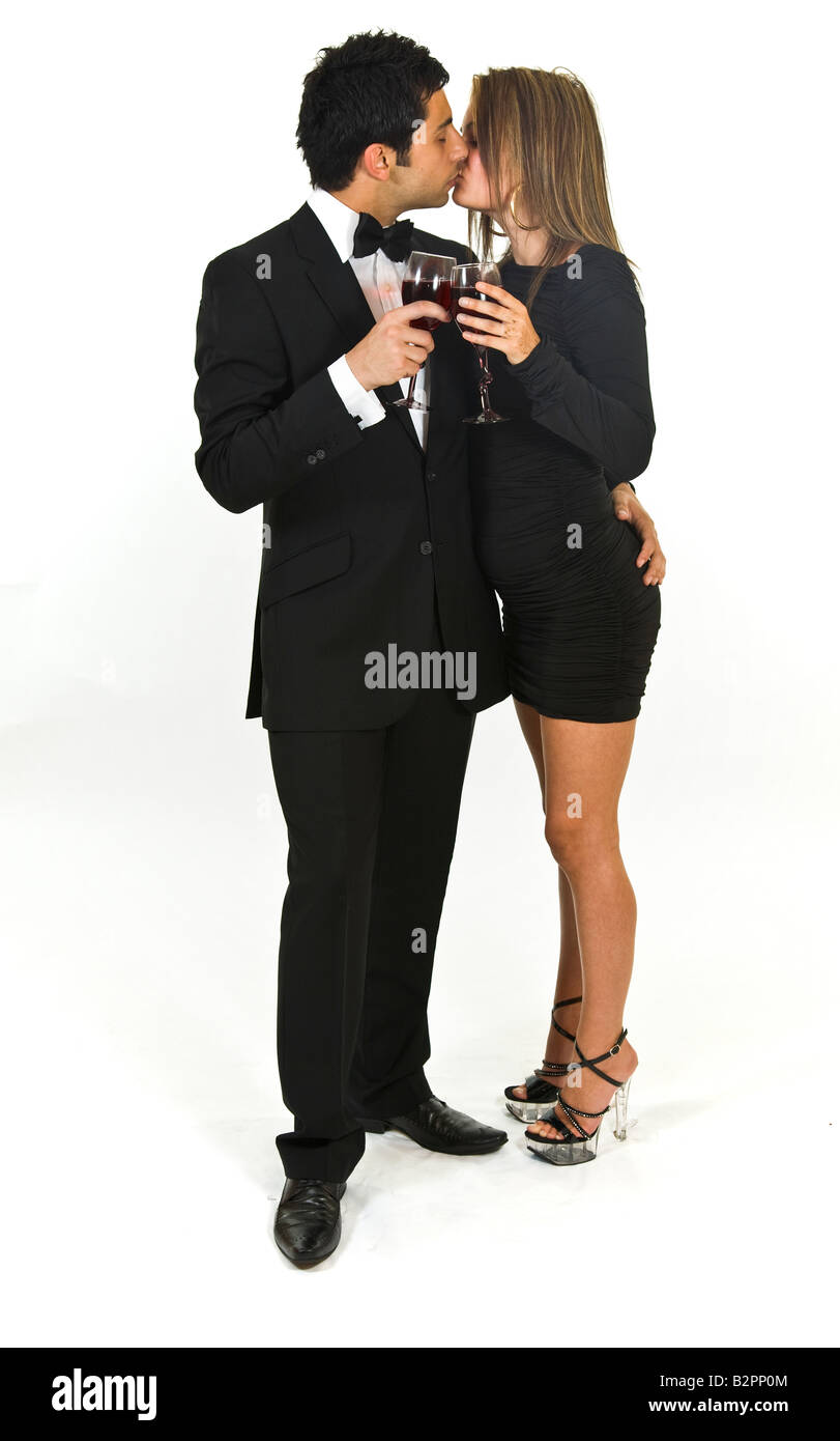Young couple in evening wear drinking red wine. - Stock Image