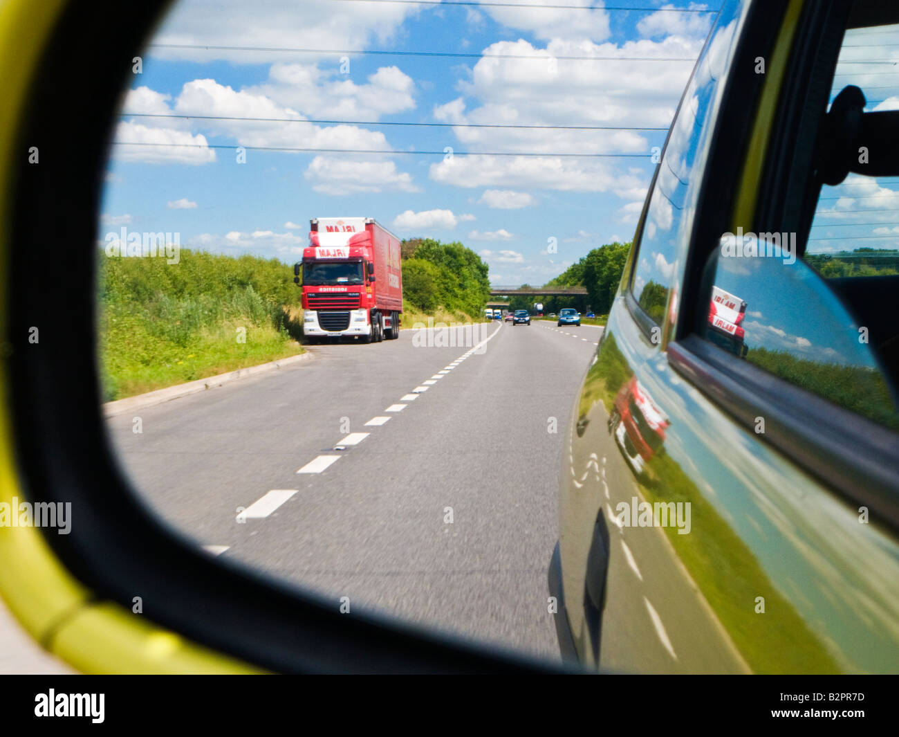 Looking at the road behind - rear view of an English dual carriageway road through a car wing mirror UK - Stock Image