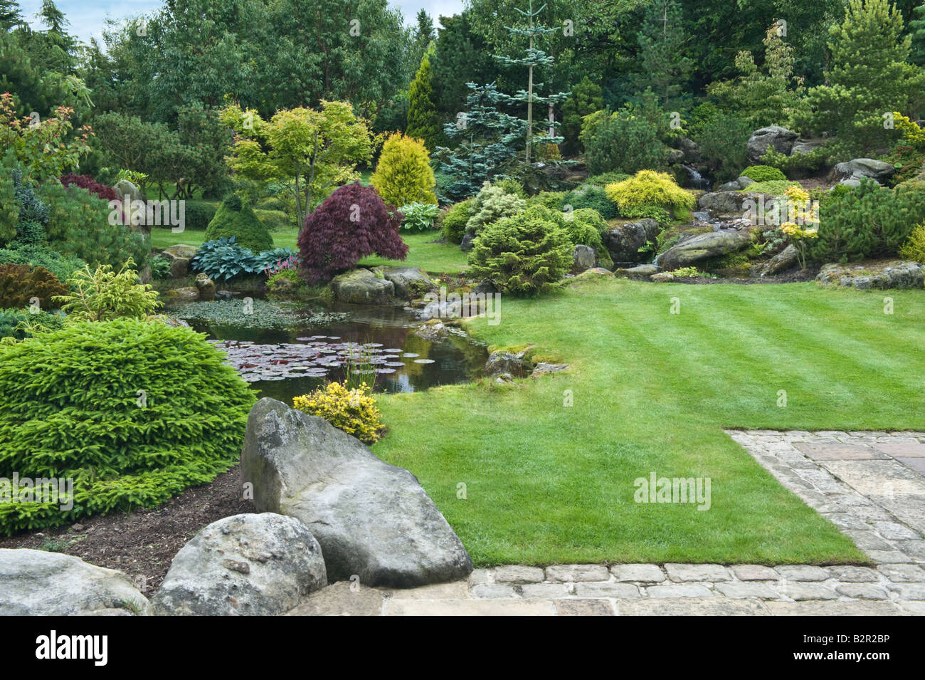 Gridstone rock with plants patio and pond in garden design by Bahaa Seedhom North Yorkshire England May - Stock Image