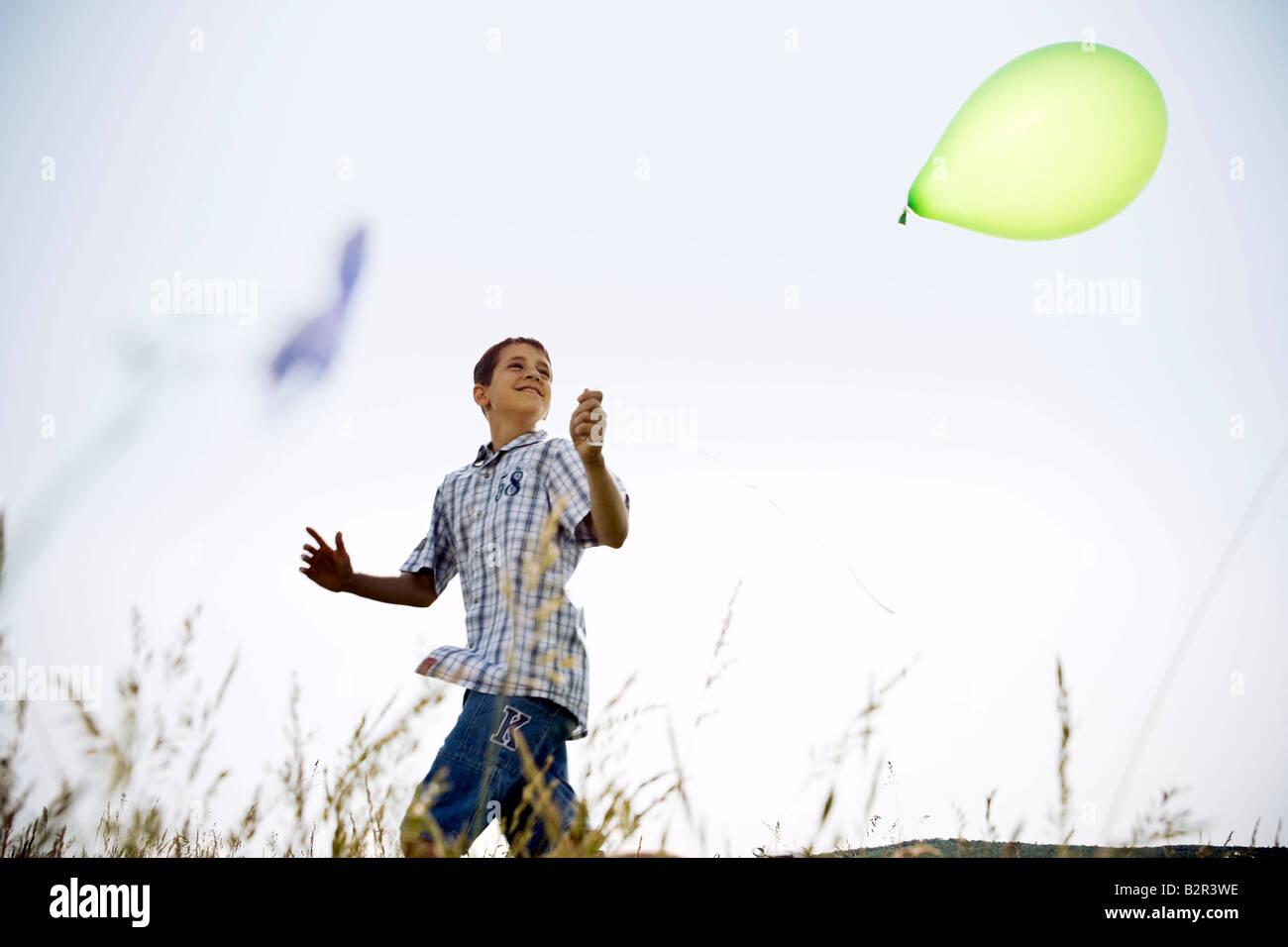 Boy running with balloon - Stock Image