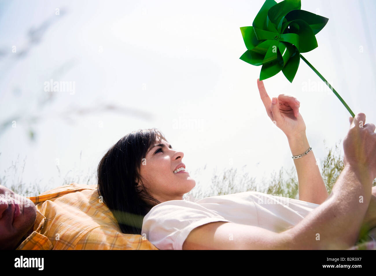 Woman in grass with windmill - Stock Image