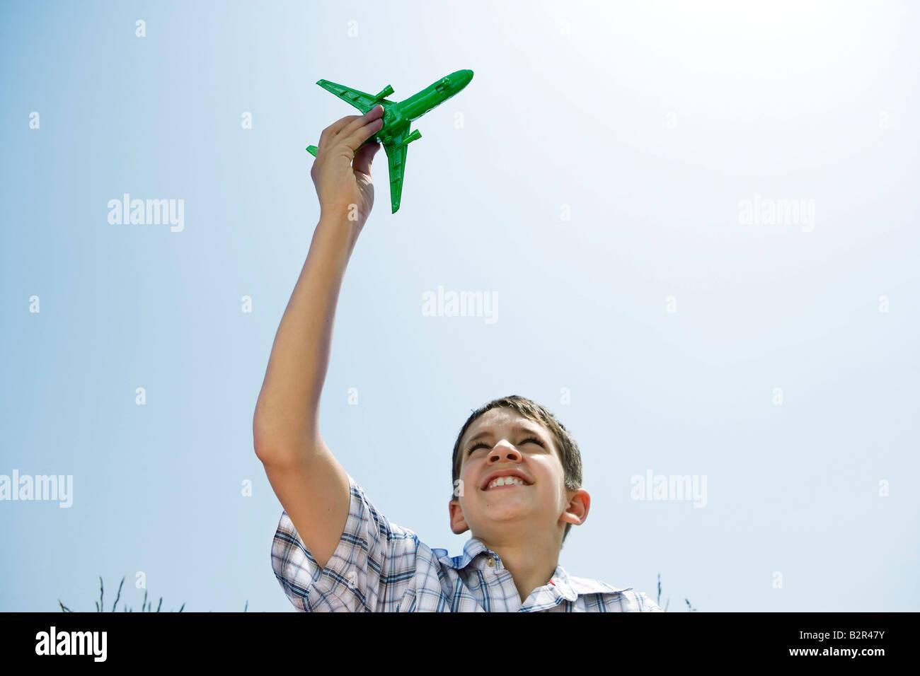 Boy holding toy plane aloft - Stock Image