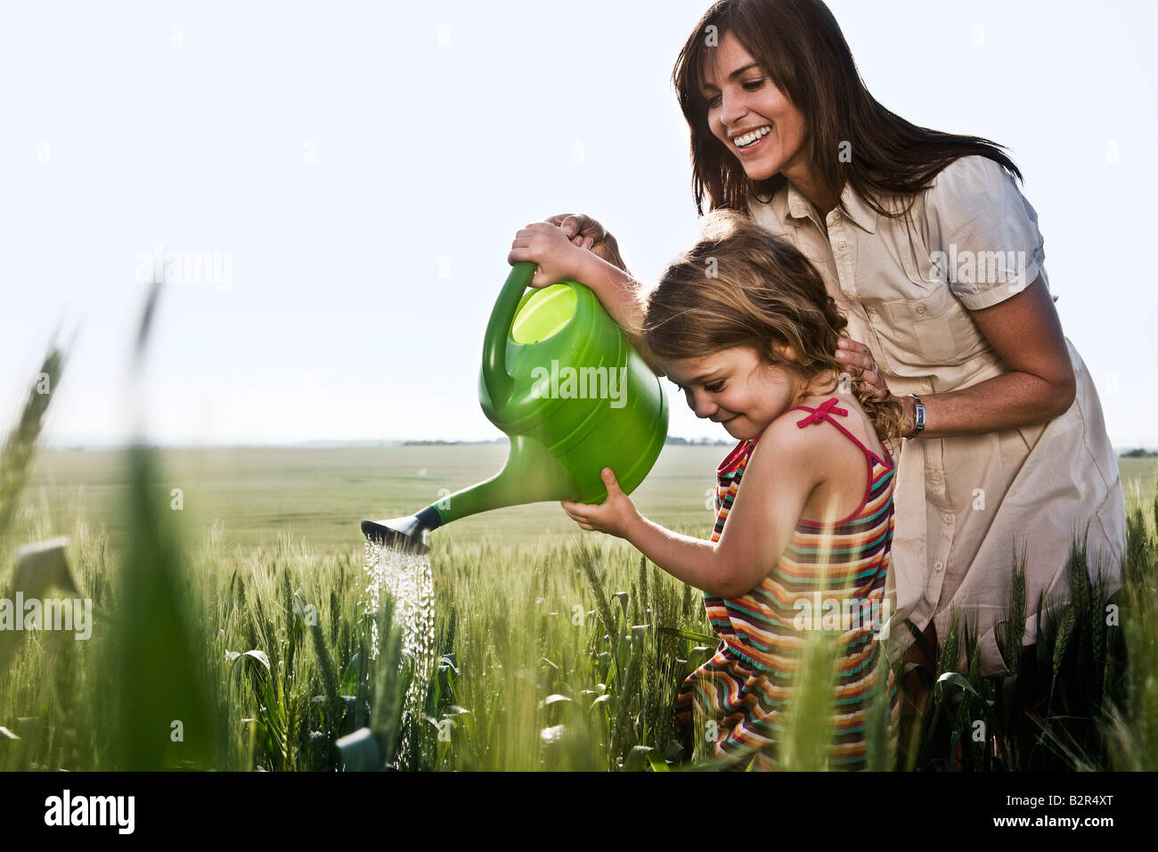 Woman helping child with watering can - Stock Image