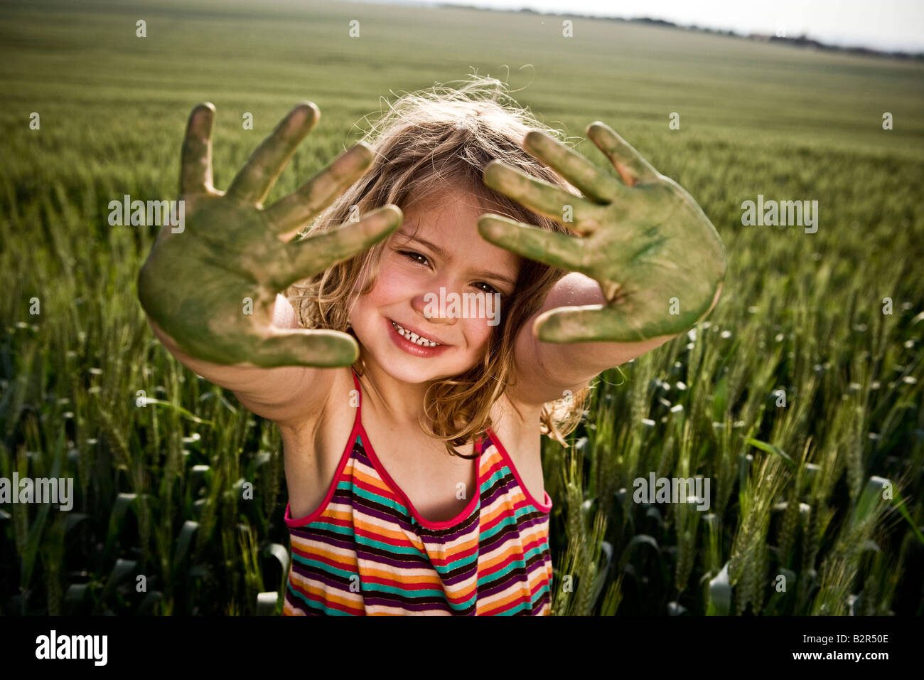 Girl with painted green hands - Stock Image