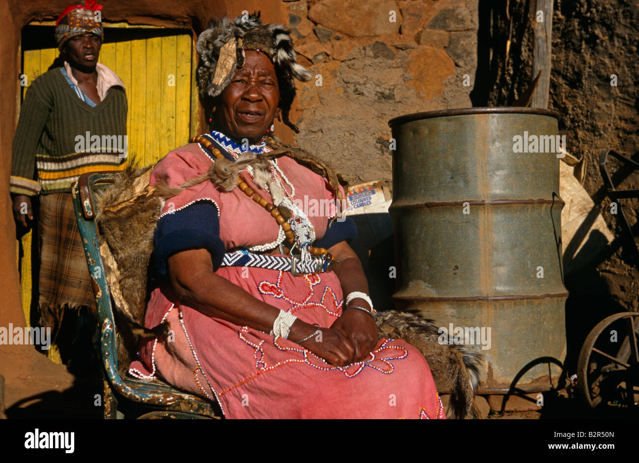 Sangoma (traditional healer) sitting in front of house