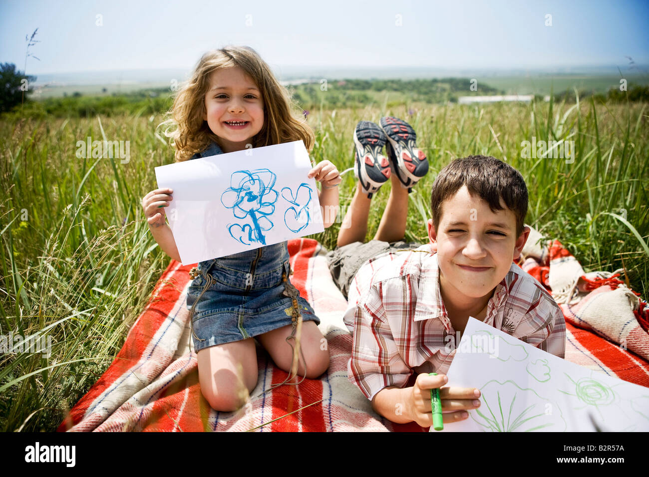 Two children showing their drawings - Stock Image
