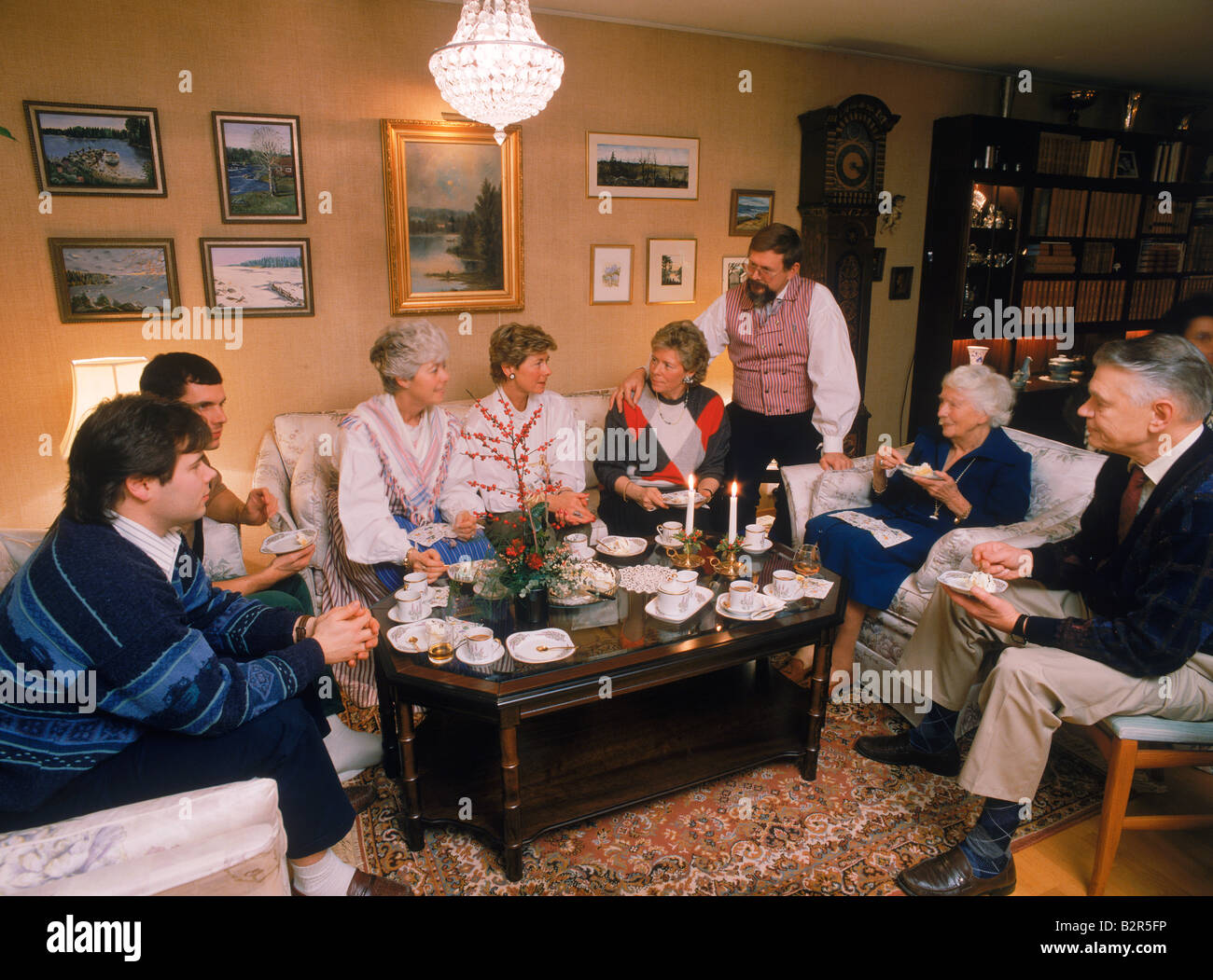 Family sharing food, coffee and conversation in frontroom of typical apartment in Stockholm Stock Photo