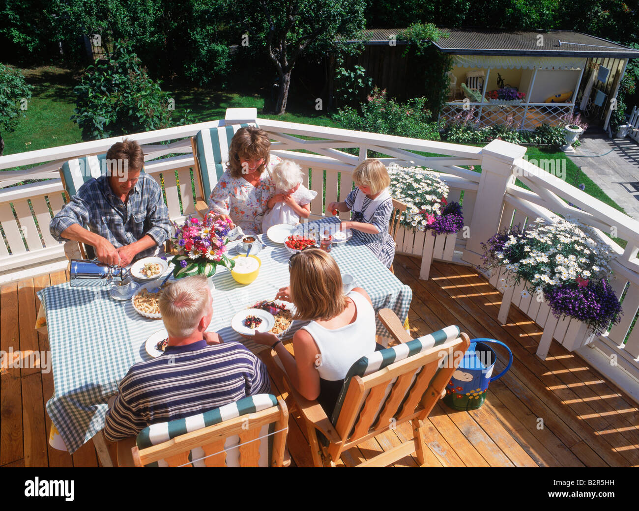 Friends sharing food, coffee and conversation on balcony of Swedish family home in summer Stock Photo