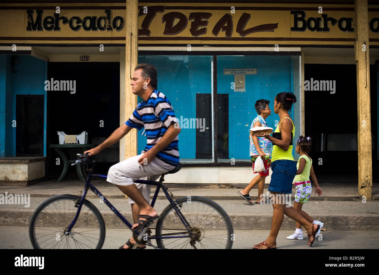 People go past a store with empty displays called Market Ideal in Baracoa Cuba - Stock Image