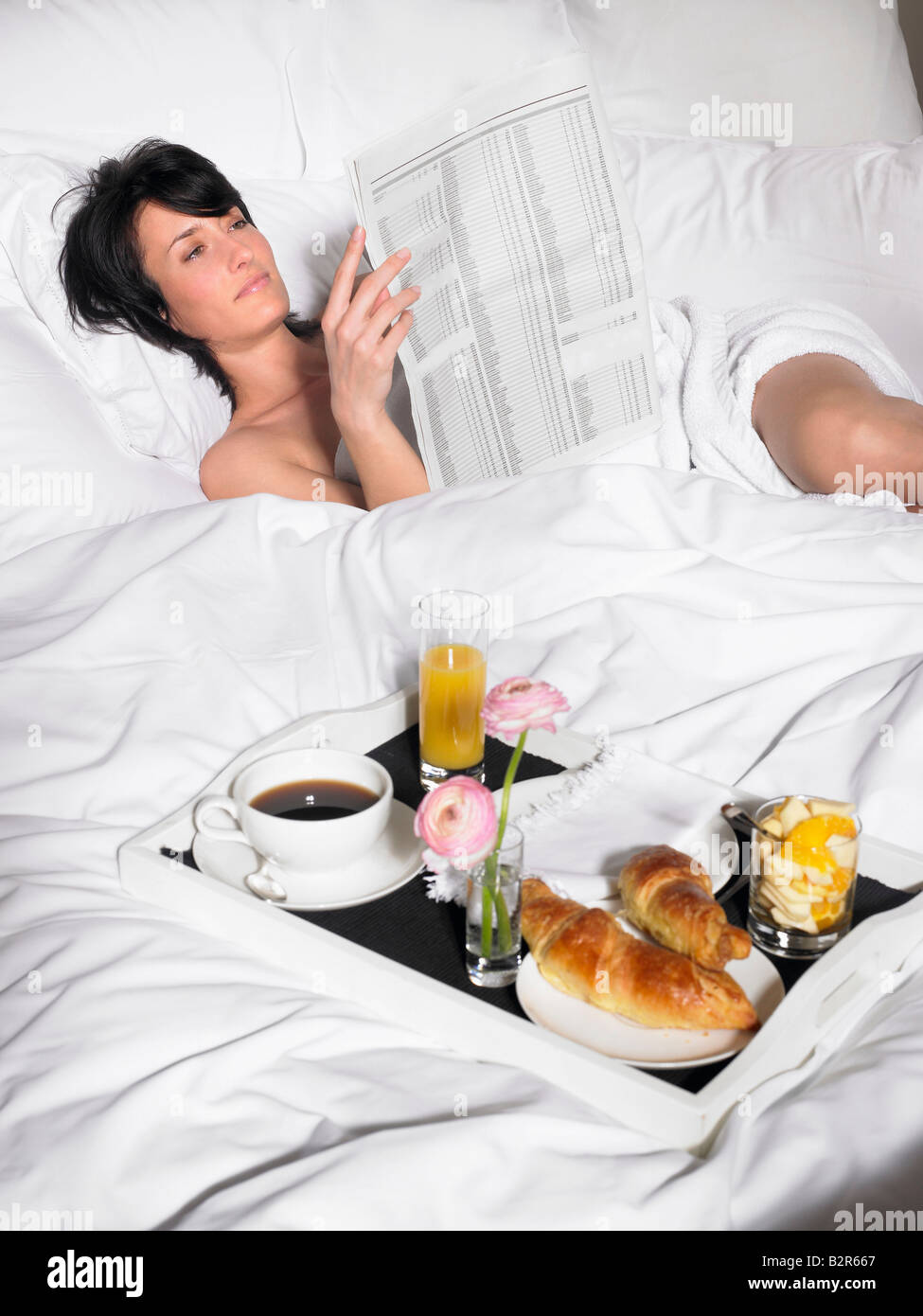 Woman reading newspaper in bed Stock Photo