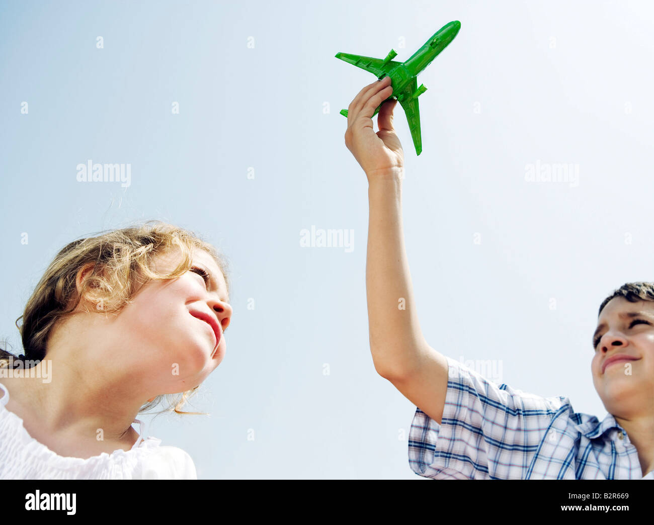 Boy and girl looking up at toy plane - Stock Image