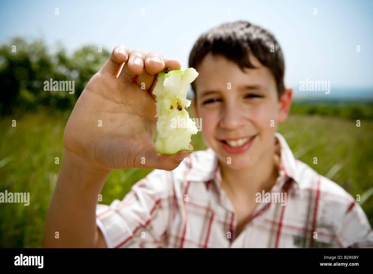 Boy holding up apple core - Stock Image