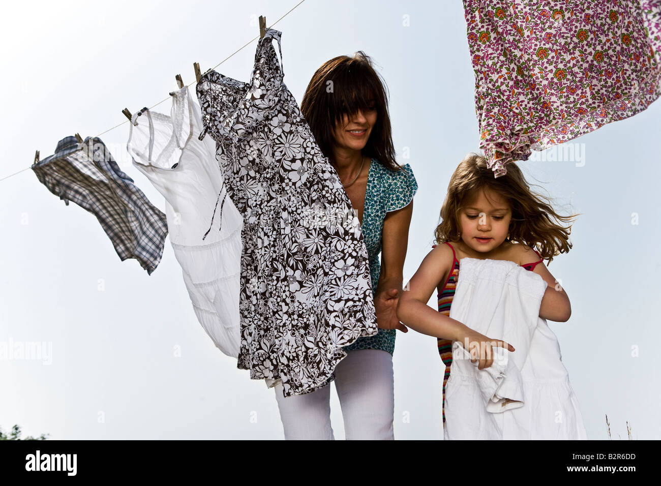 Girl helping mother fold clothes - Stock Image