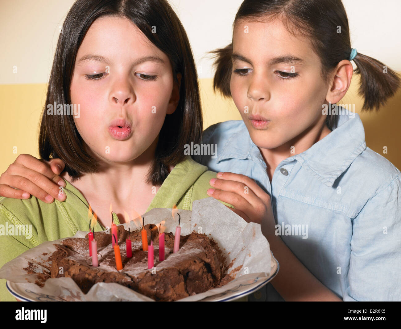Girls holding a birthday cake - Stock Image