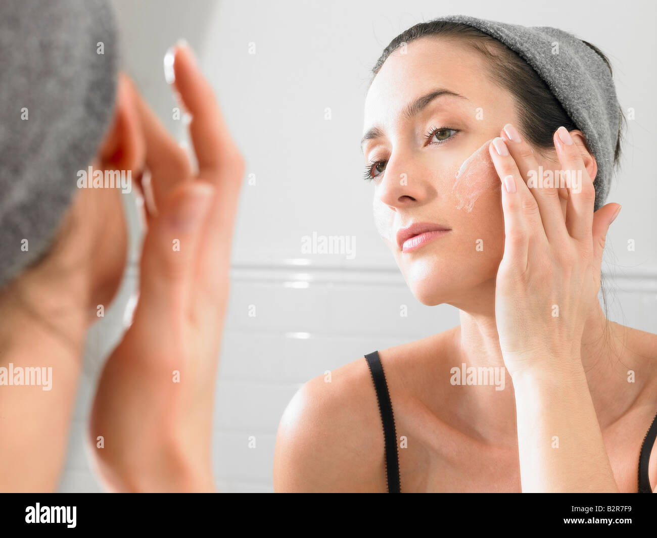 Woman putting on face cream - Stock Image