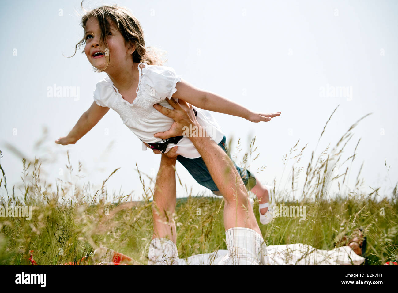 Girl held aloft flying - Stock Image