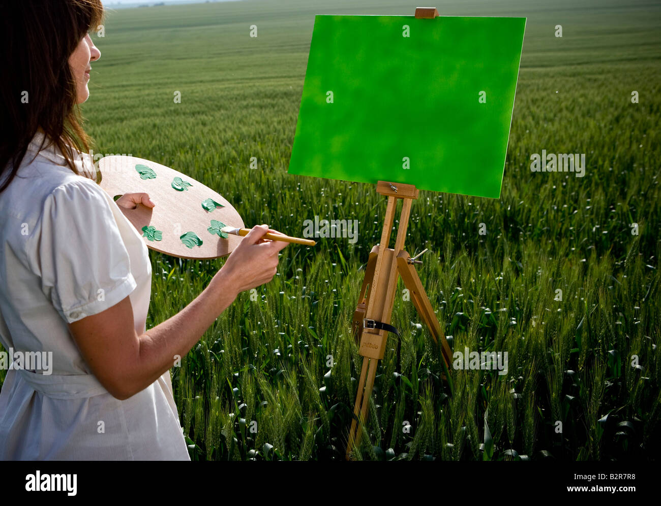 Woman painting in wheat-field - Stock Image