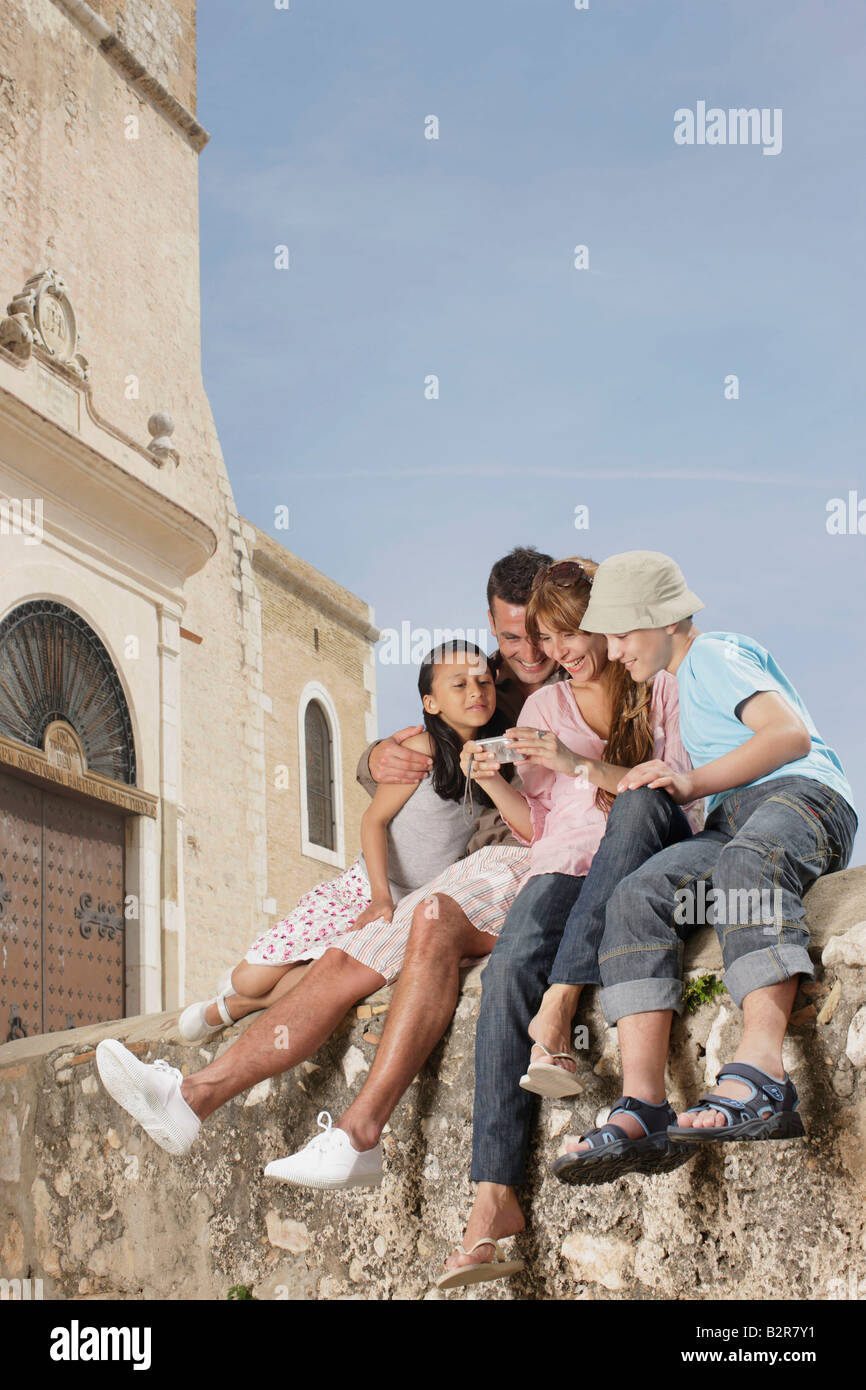 Family sitting on wall sharing photos - Stock Image