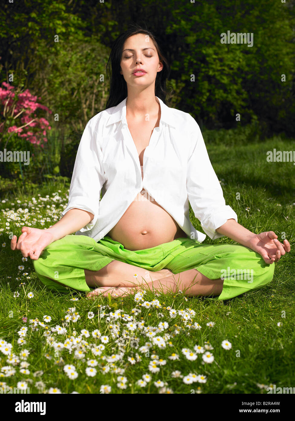 Pregnant woman in a yoga session - Stock Image