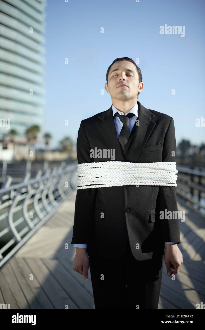 Business man tied up with ropes outdoors - Stock Image