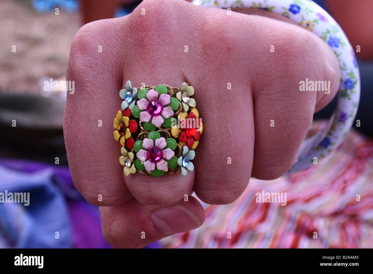 A close-up of a colourful ring on a clenched fist - Stock Image