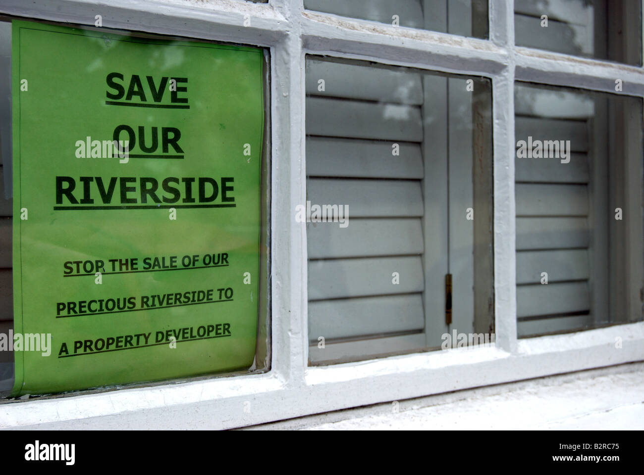 green sign with black text on a residential window in twickenham, england, opposing the dsale of riverside land Stock Photo