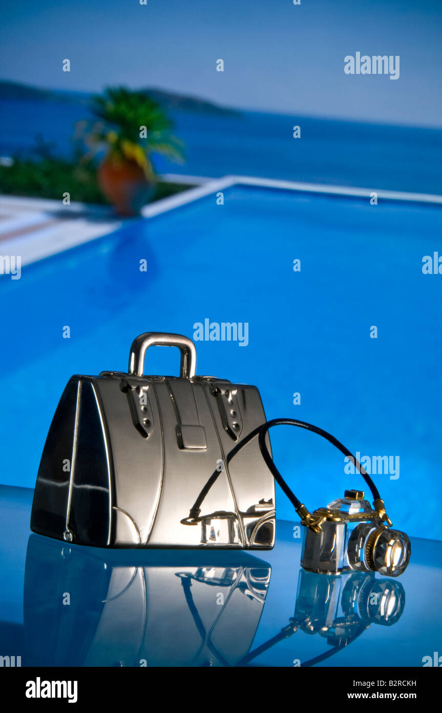 Luxury holiday vacation bling concept, Silver suitcase and crystal camera with private infinity pool and sea in - Stock Image