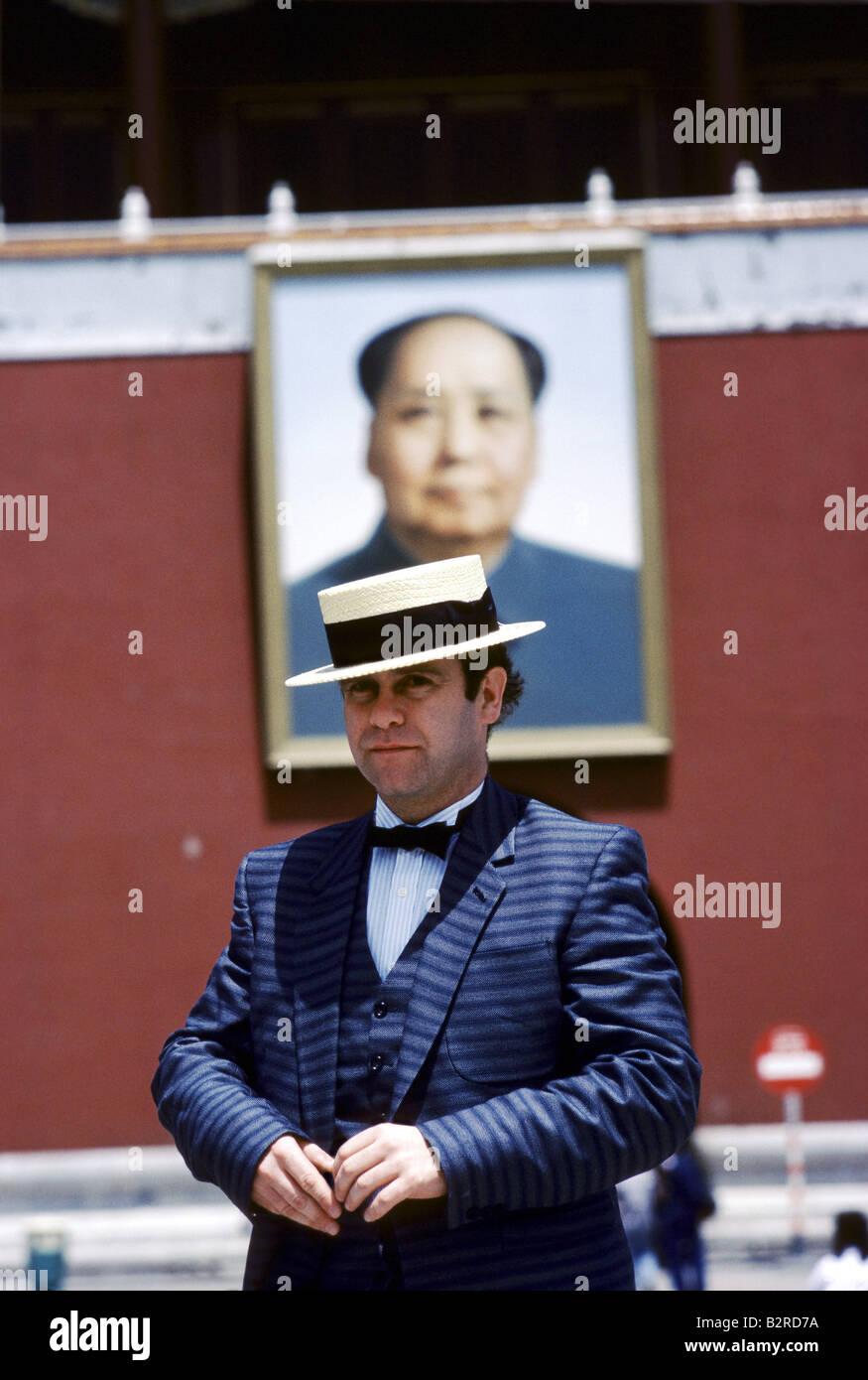 British pop singer Elton John wearing gentleman s suit hat in Tiananmen Square Mao s portrait in background - Stock Image