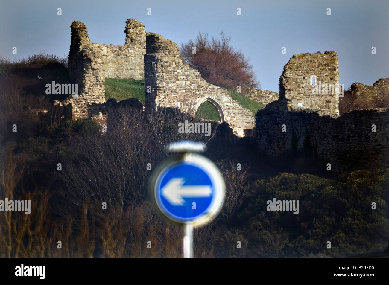 A Keep Left road sign in front of the ruins of the Norman Castle in Hastings East Sussex. - Stock Image