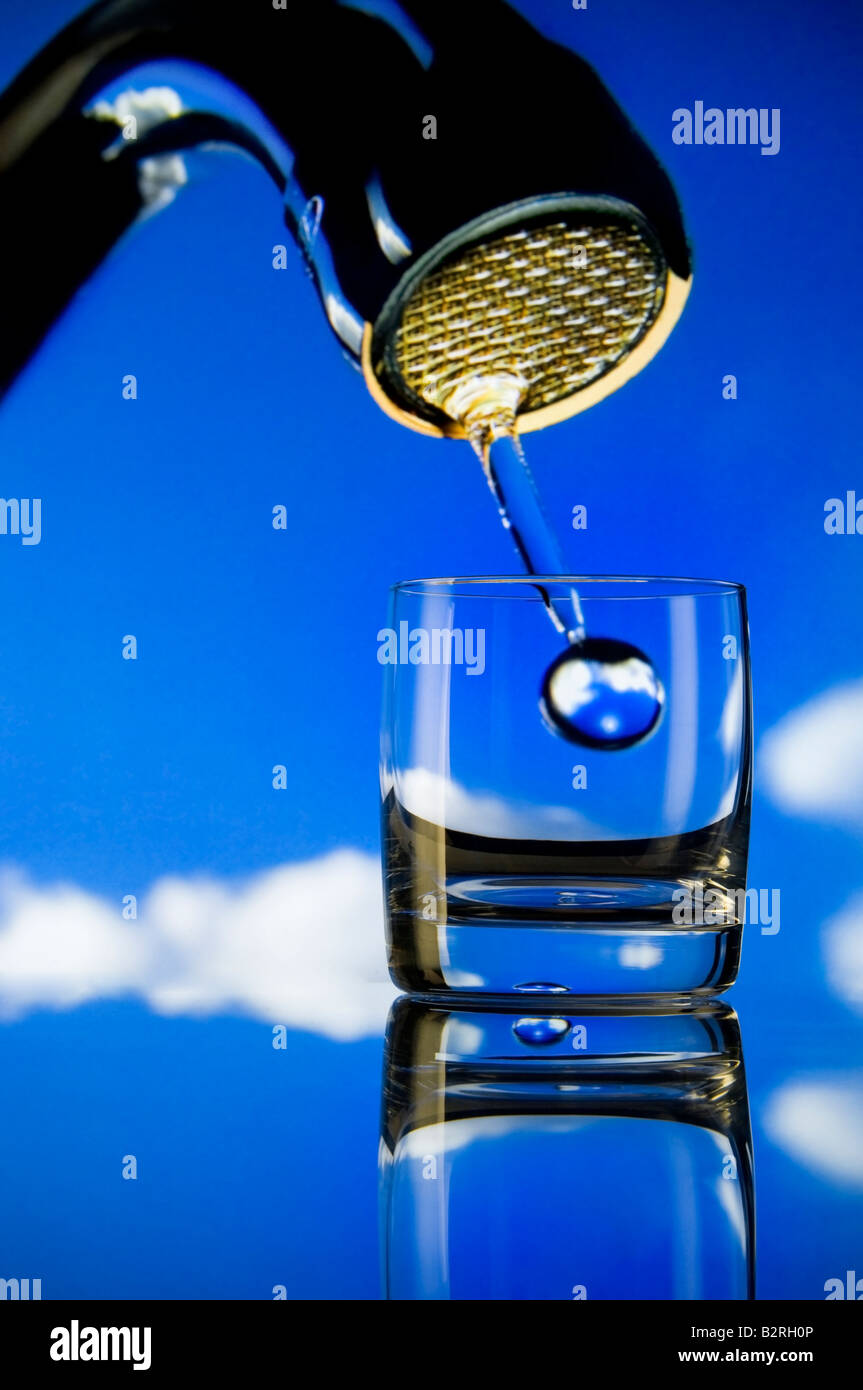 Concept conservation issues Large droplet of water from big tap falling into a small glass - Stock Image