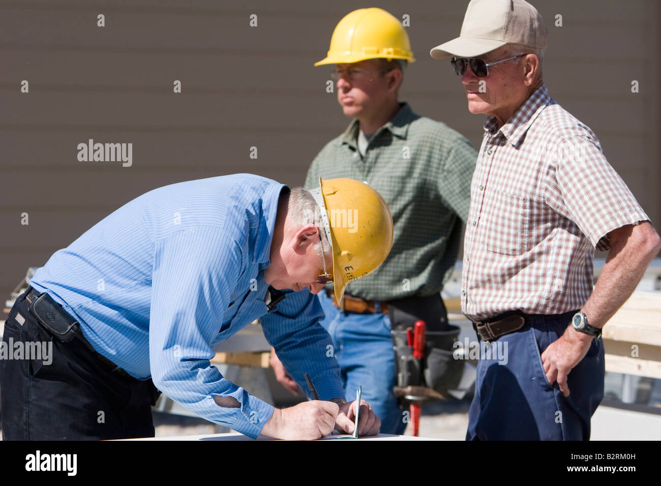 A construction foreman signs paperwork on a job site - Stock Image