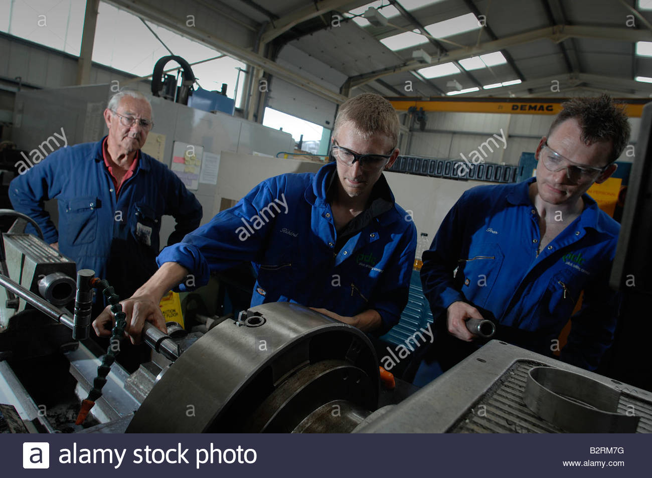 Engineering apprentices under guidance from an instructor - Stock Image