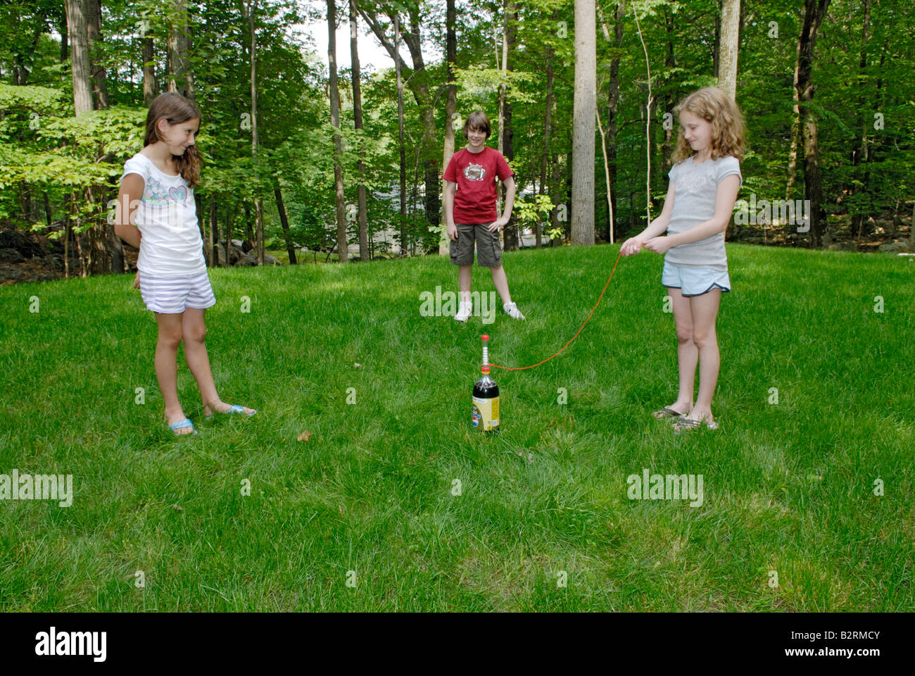 Kids making a Mento's Fountain chemistry demo in the backyard - Stock Image