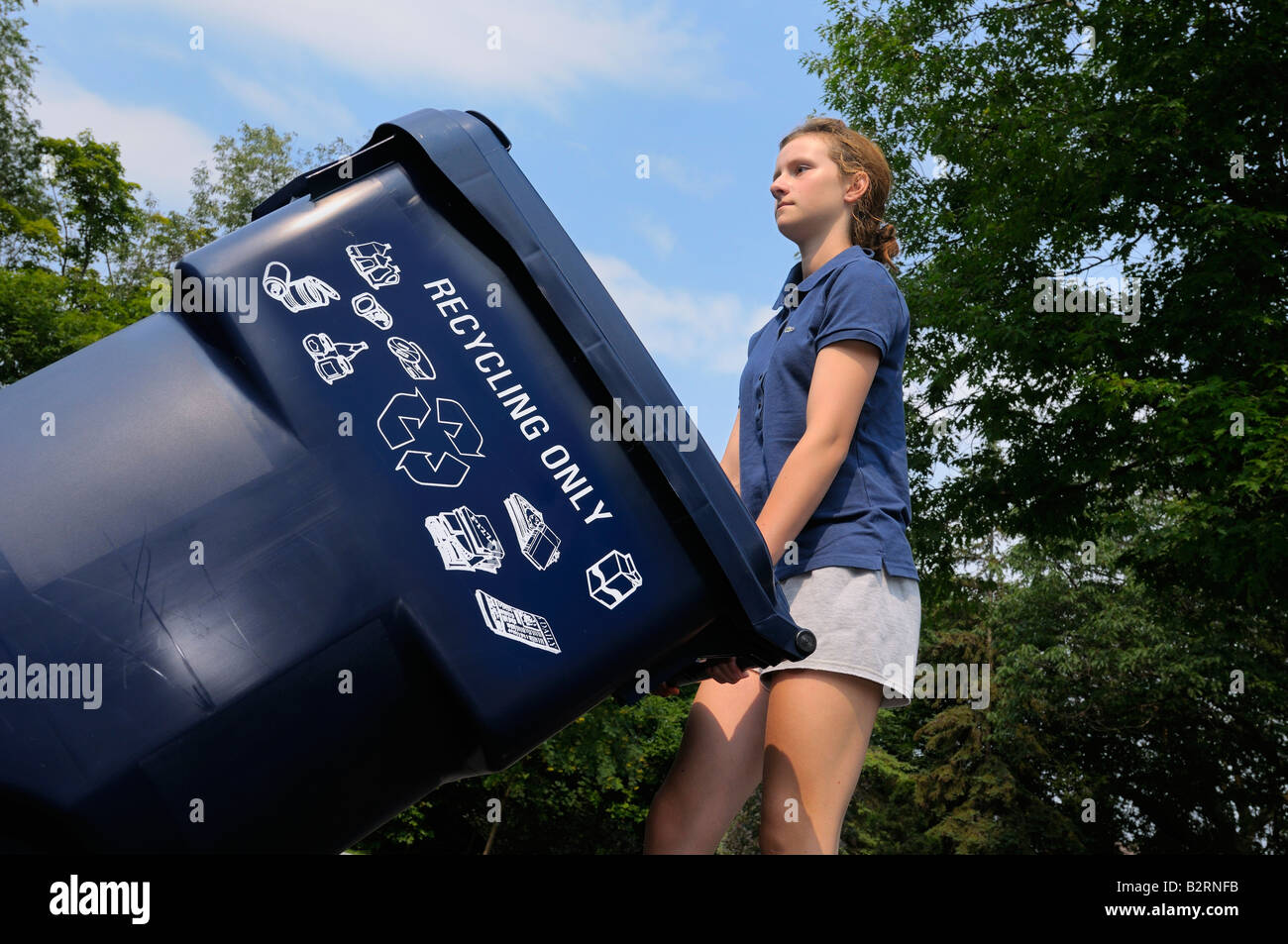 Young girl taking out the household blue recycling bin to the curb in Toronto - Stock Image