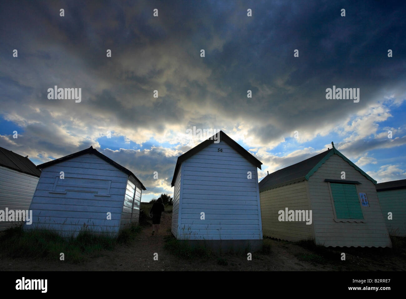 Child walking betwenn beach huts under a stormy sky. Stock Photo