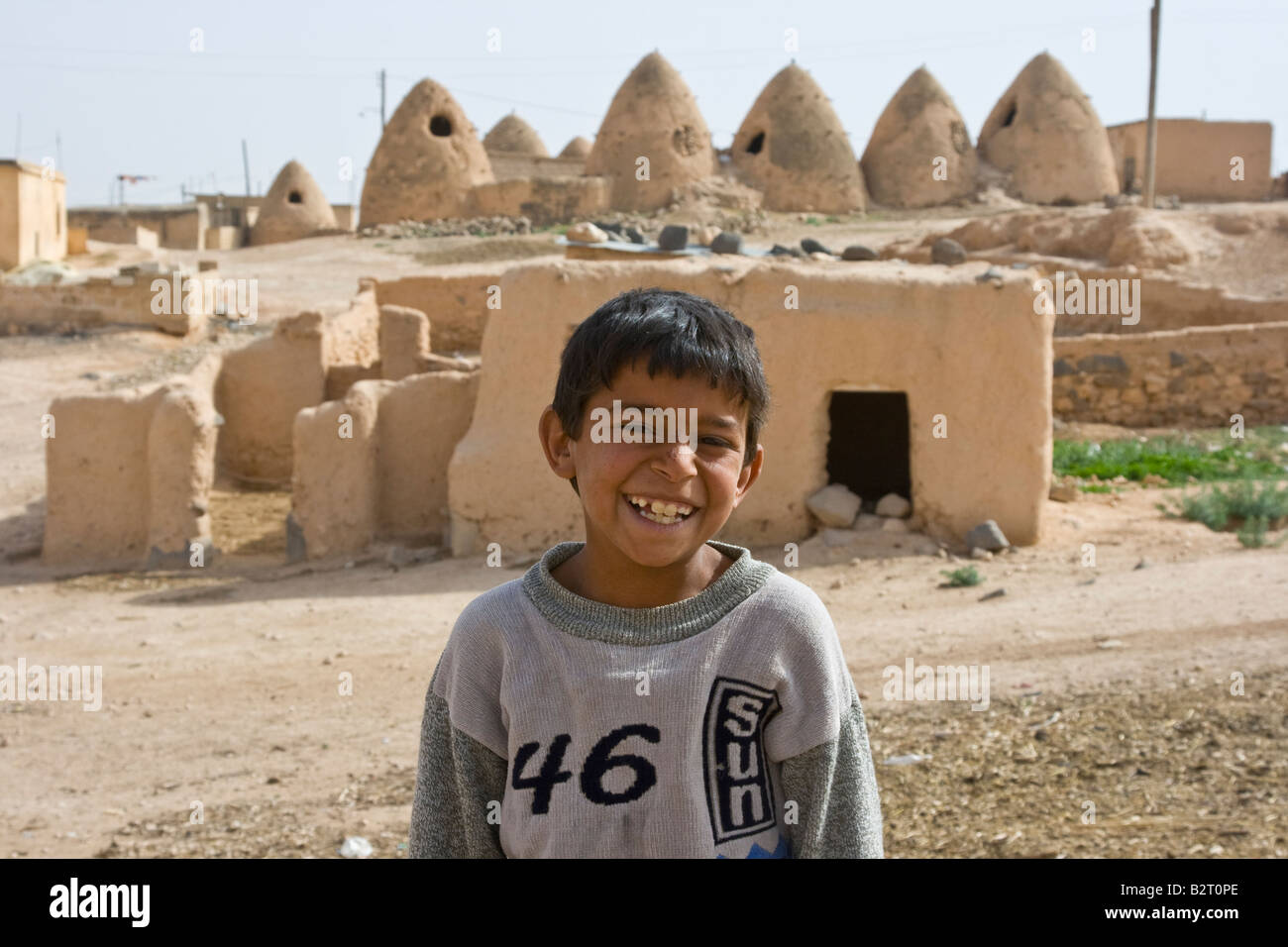 Arab Boy in front of Ancient Beehive Houses in Syria Stock Photo