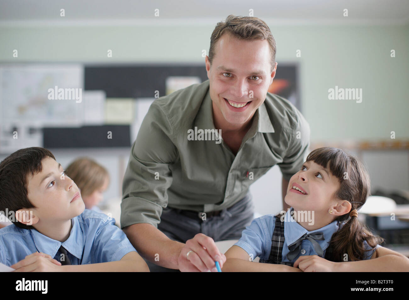 Male teacher correcting student work - Stock Image