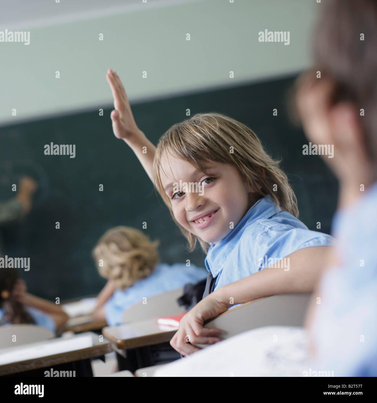 School boy raising hand in class Stock Photo