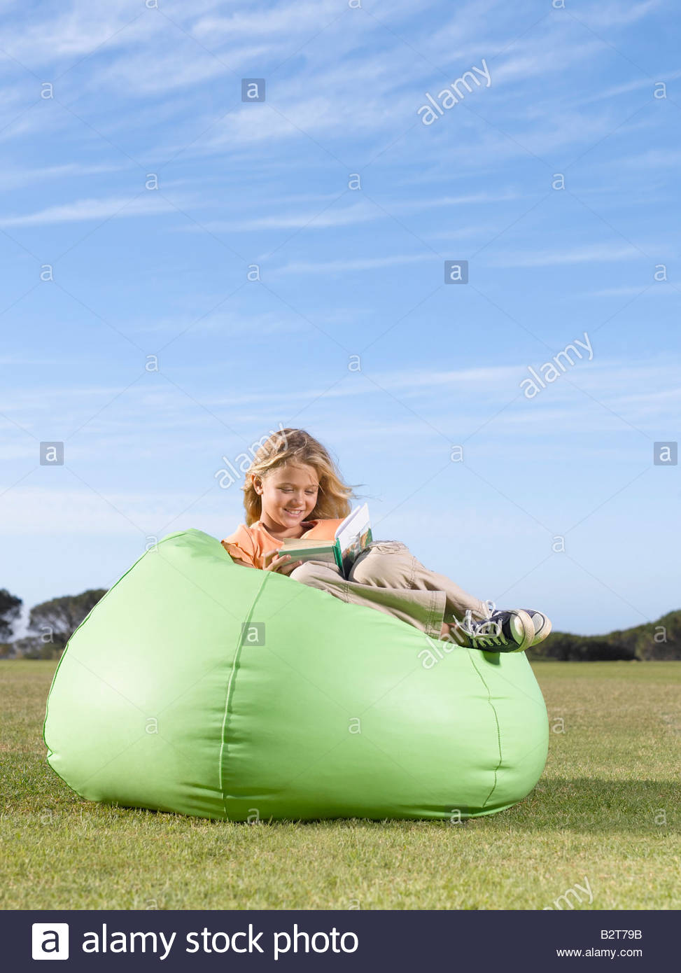 Young girl in bean bag reading outdoors - Stock Image