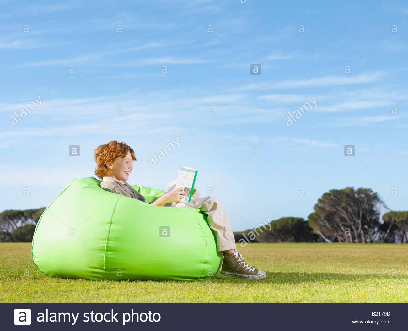 Young boy in bean bag reading outdoors - Stock Image