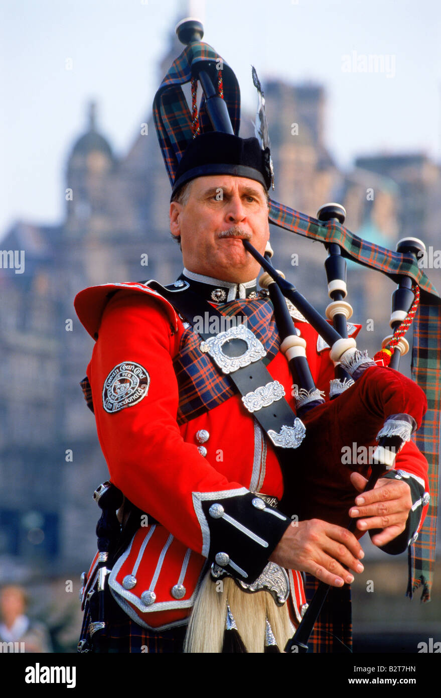 Bagpiper playing near Scott Monument at city center of Edinburgh, Scotland - Stock Image