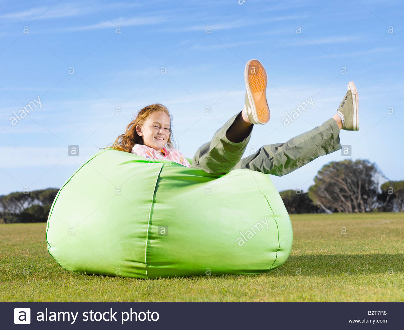 Young girl relaxing in bean bag outdoors - Stock Image