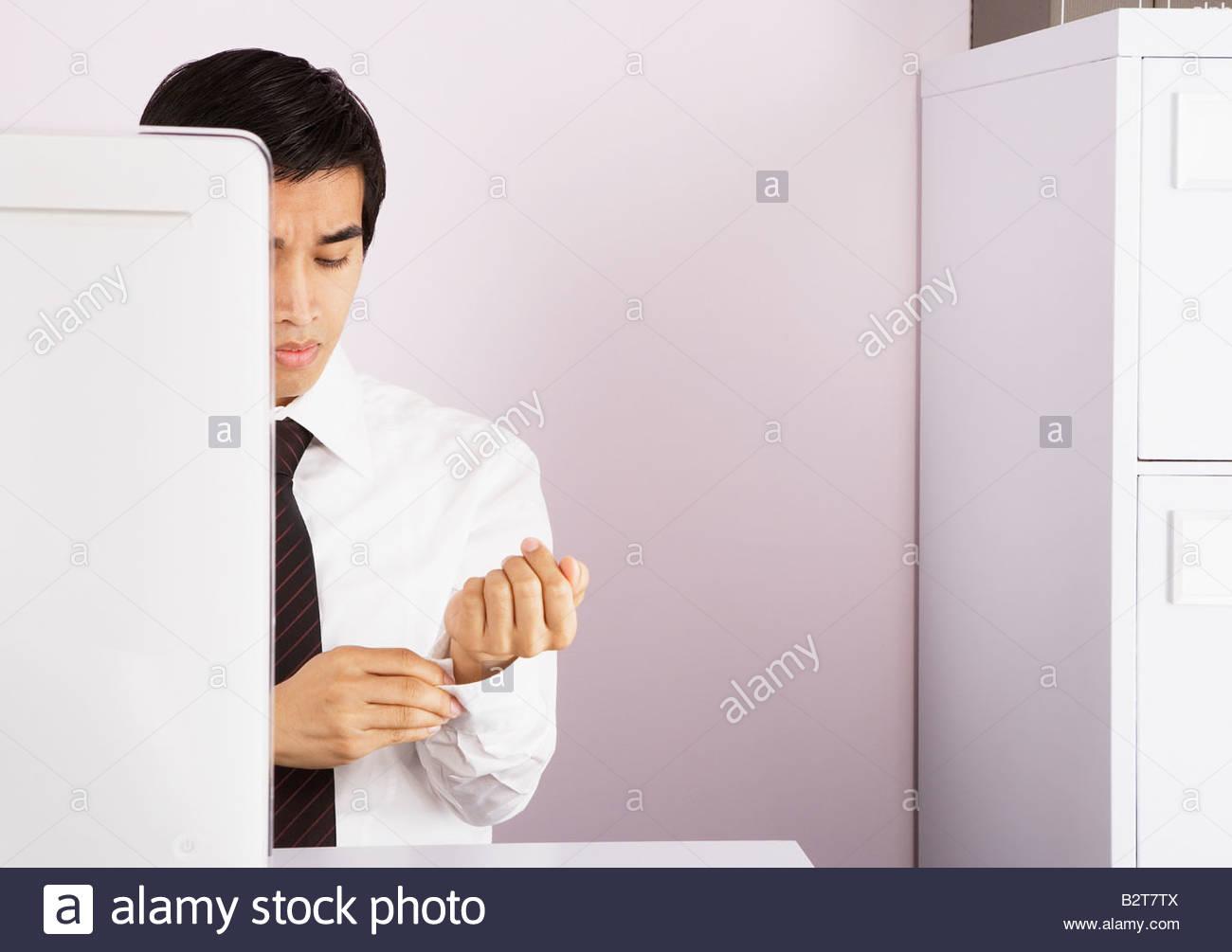 Businessman fastening his shirt cuff - Stock Image